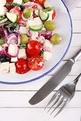 Greek salad served in plate on wooden background