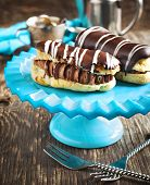 foto of eclairs  - Chocolate Eclairs And Cup Of Espresso on the table - JPG