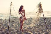 attractive young woman stand on sandy beach by fishing net at sunset full body shot