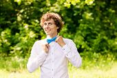 Curly Man In White Shirt And Blue Bow Tie Smiling