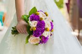 Bride Holding Violet Wedding Carnation Bouquet Against Gown