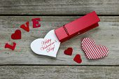 Happy Valentine's Day in clothespin by red hearts