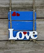 Love text on antique blue wood sign hanging on wooden fence
