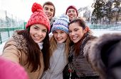 people, friendship, technology, winter and leisure concept - happy friends taking selfie with smartphone or camera outdoors