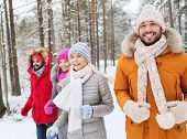 love, relationship, season, friendship and people concept - group of smiling men and women running in winter forest