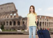 travel, holiday, vacation, childhood and transportation concept - smiling little girl with suitcase over coliseum background