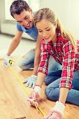 repair, building and home concept - smiling couple measuring wood flooring