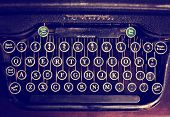 an antique typewriter on a wooden table toned with a retro vintage instagram filter effect app or action