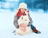 Christmas, Winter And People Concept - Happy Teenager Boy With White Samoyed Dog Outdoors In Winter
