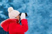 Woman Photographer Takes Picture On The Digital Camera Outdoors In Winter Cold Day