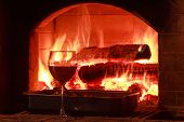 Glass of red wine at firewood oven background