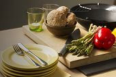 Bread, Veggies, Knife, Glass And Plates On Table