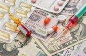 A syringe and medicaments on dollar bills