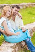 Portrait Of Happy Caucasian Couple Sitting Together Outdoors While Using Pda Handheld