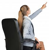 Businesswoman on office chair, pointing finger up and ahead