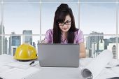 Female Engineer Working At Desk In Office