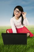 Little Girl With Laptop At Field