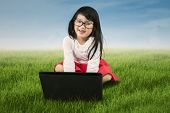 Lovely Little Girl With Laptop At Meadow