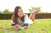 Portrait Of Beautiful Young Woman Lying On Green Grass Field And Holding Modern Smart Phone In Hand