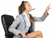 Businesswoman in headset sitting on office chair touching or pressing something