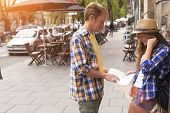 Young couple attractive tourist watching map. Dating and tourism concept. Summer holidays.
