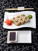 California Rolls Sushi With Pickled Ginger, vasabi And Soy Sauce In The Plate