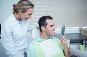 Smiling young man looking at mirror in the dentists chair