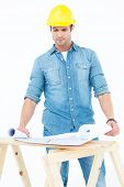 Handsome architect analyzing blueprint at table over white background