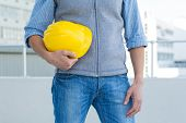 Cropped image of male architect holding yellow hard hat outdoors