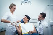 Male dentist with assistant shaking hands with woman in the dentists chair