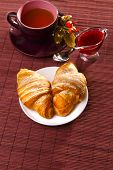 Croissants, hot tea and jam with flowers