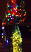 Christmas lights in bottles on wooden background