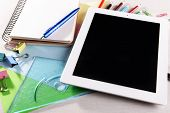 Tablet PC with office supplies on desktop background