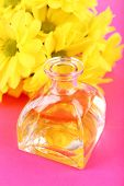 Bottle of perfume with yellow chamomile on pink background