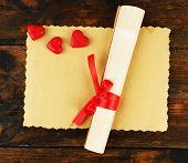 Roll and sheet of paper with hearts on rustic wooden table background