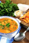 Composition with carrot soup, ingredients and herbs on color wooden background