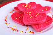 Cookies in form of heart on plates background