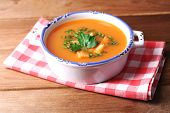 Carrot soup  in bowl, on wooden background
