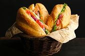 Sandwiches with salmon in wicker basket, on dark background