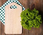 Cutting board with lettuce on wooden planks background