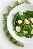 Salad with quail egg and basil in plate isolated on white