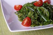 Seaweed salad with slices of cherry tomato on bamboo mat background