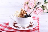 Dessert with prunes in cup with bouquet of roses on color wooden table background