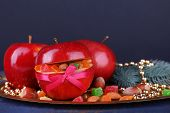Christmas red apples stuffed with dried fruits on metal tray on color wooden table and dark background