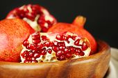 Juicy ripe pomegranates in wooden bowl, on dark background