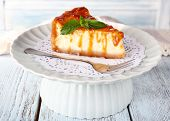 Cheese cake on paper napkin on plate on wooden background