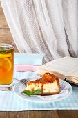 Cheese cake in plate, cup of tea and books on tablecloth on curtain background