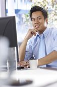 Happy Asian businessman working with computer, sitting at desk in office, smiling, looking away.