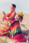 Toned photo of son and mother dressed in Mexican clothes praying together