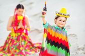 Boy dressed in Mexican costume and holding a toy gun